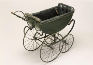 Photo of 19th century pram shaped like a half-circle on delicate wheels